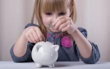 A young girl puts money in a piggy bank. Image courtesy Sofya Apkalikova/shutter