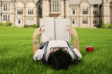 A female college student reads a book. Image courtesy Creativa/shutterstock.com