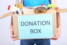 A young man holds a box of donations. Image courtesy Africa Studio/shutterstock.