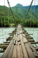 Rickety bridge over rapids. Image via Zastolskiy Victor/shutterstock.com