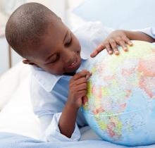 Small boy looking at his globe, wavebreakmedia / Shutterstock.com