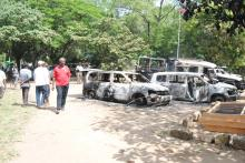 A man walks past burnt cars destroyed during a terror attack in Lamu country, Ju