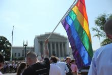 A man holds a gay pride flag in front of the Supreme Court. Image courtesy Adell