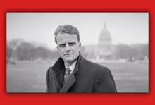 Billy Graham looks straight into the camera with the US Capitol building behind him.