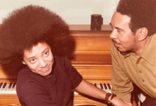 A young Nikky Finney sits at a piano with her father in 1972.