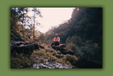 Parker Millsap sits on a rock in the forest.
