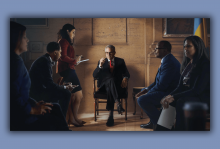 A scene from Philly DA of Larry Krasner sitting in a chair.