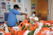 A worker hands a bag of groceries to a woman at La Casa in Mt. Pleasant, Washington, DC.
