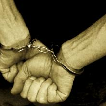 Hands in handcuffs, Digital Vision. / Getty Images