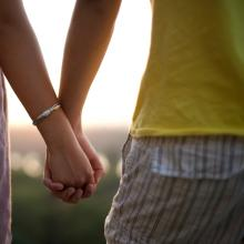 A couple holding hands. Image via Mirko Tabasevic/shutterstock.com