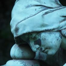 Grave marker showing face of sorrow, Hub.-Wilh. Domroese / Shutterstock.com