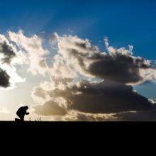 Man praying against cloudy sky, Dayna More / Shutterstock.com