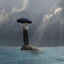 Man with an umbrella in a flood, photobank.kiev.ua / Shutterstock.com