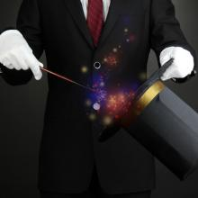 Magician performing on dark background, Africa Studio / Shutterstock.com