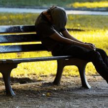 An impoverished young man man on a bench. Photo courtesy Dariush M/shutterstock.