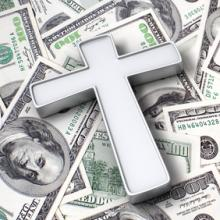 Cross on top of $100 bills, StockThings / Shutterstock.com