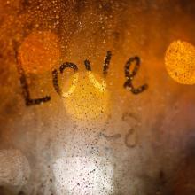 'Love' written on window in the rain, Wolf__ / Shutterstock.com