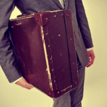 A young man carries an old suitcase. Image courtesy nito/shutterstock.com.