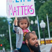 A young girl joins a rally against racism in Washington, DC in August 2014. Imag