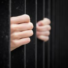 Hands on prison bars. Image courtesy Kaspars Grinvalds/shutterstock.com