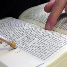Student pointing at bible, Nir Levy/Shutterstock.com.