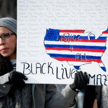 Woman holds a 'Black Lives Matter' sign. Image courtesy Rena Schild/shutterstock