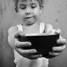 Child holding empty bowl, Suzanne Tucker / Shutterstock.com