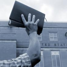 Man holding up Bible in front of court house, Cheryl Casey / Shutterstock.com