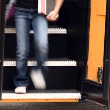 Youth getting off a school bus,  Margie Hurwich / Shutterstock.com