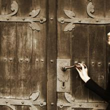 Photo: Young woman near church doors, Lisa A / Shutterstock.com