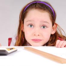 Girl working on math homework. Image by Cheryl Casey/Shutterstock.com.