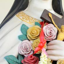 Flowers and crucifix in the hand of holy women. Image via GOLFX/shutterstock.com