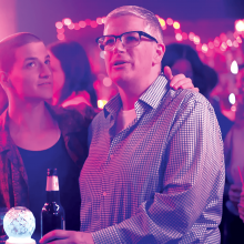 A scene from 'Work In Progress' shows Abby, the main character, at a club in pink light.