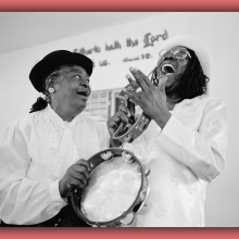 A vintage photo of two Black women laughing and playing instruments in church.