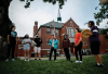 A group of Indigenous elders and students stand in a circle praying in front of a red-brick residential school.